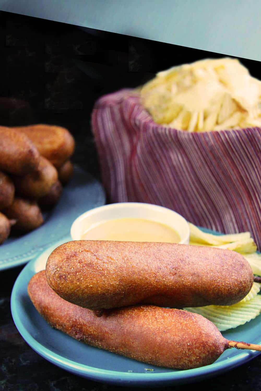 two golden corn dogs on a blue plate with honey mustard sauce