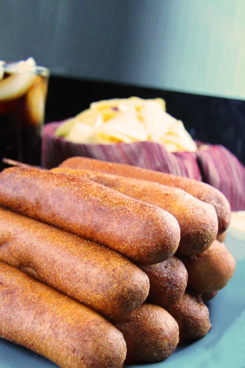 up close side view of homemade corn dogs stacked o top of each other