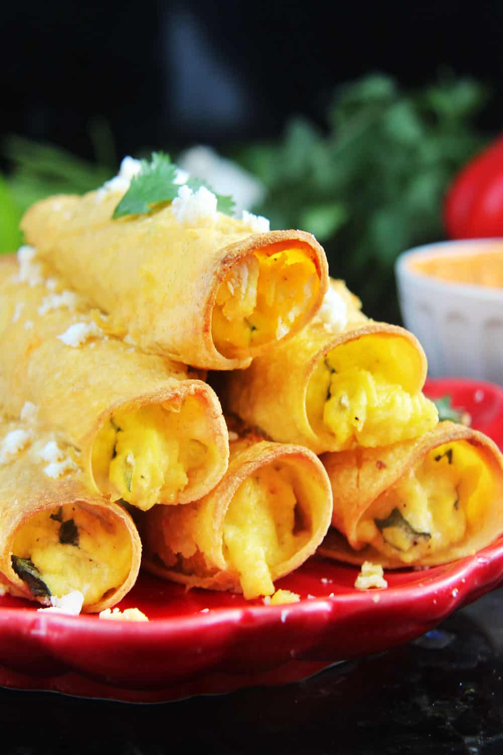 Breakfast Taquitos on a red plate stacked in a pyramid.