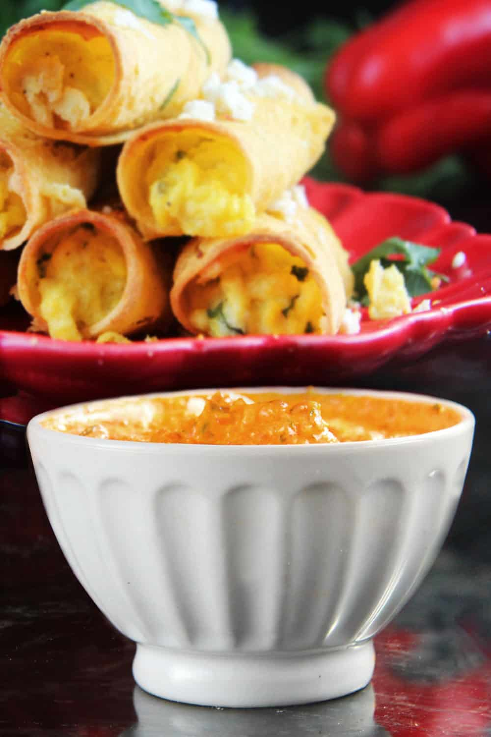 Breakfast Taquitos on a red plate focusing on the red pepper and feta dipping sauce in a white serving bowl.