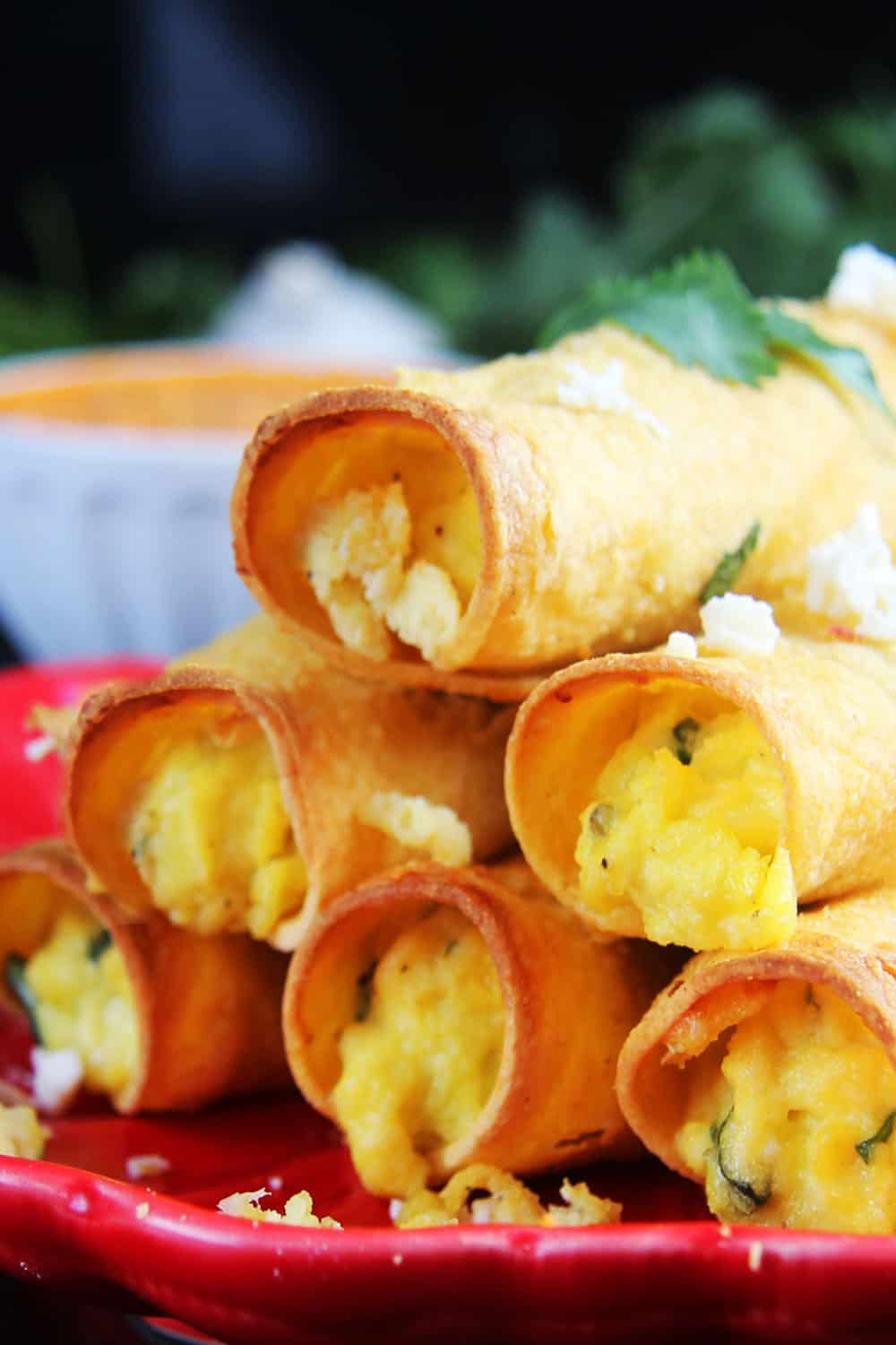 Close up photo of Breakfast Taquitos on a red plate stacked up.