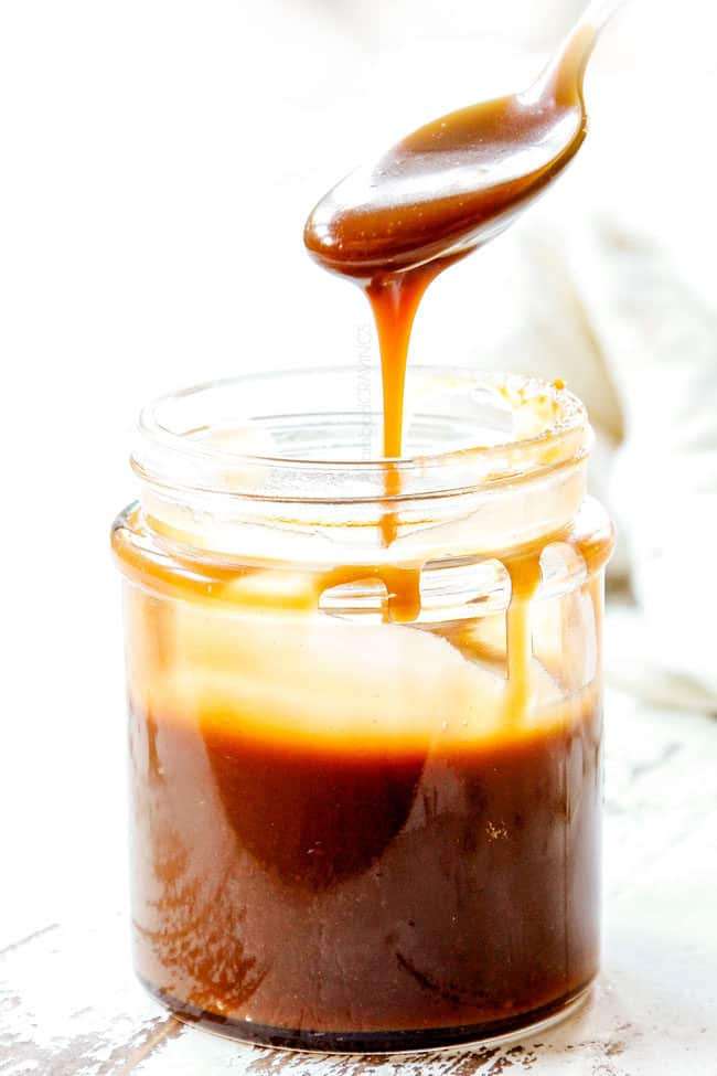 far away of a spoon full of the best caramel drizzling down into a glass jar