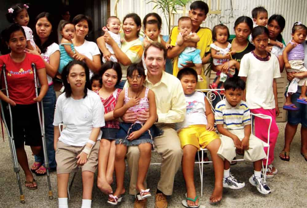 Gary Sabin surrounded by children in the Philippines with Sabin Children's Foundation