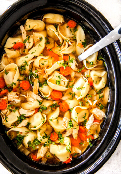 cheese tortellini, carrots, celery, onions, garlic and spices in crockpot with soup ladle for This is the BEST Slow Cooker Chicken Tortellini Soup you will ever try!  It's super easy, seasoned to perfection and a comforting, satisfying dinner any night of the week!