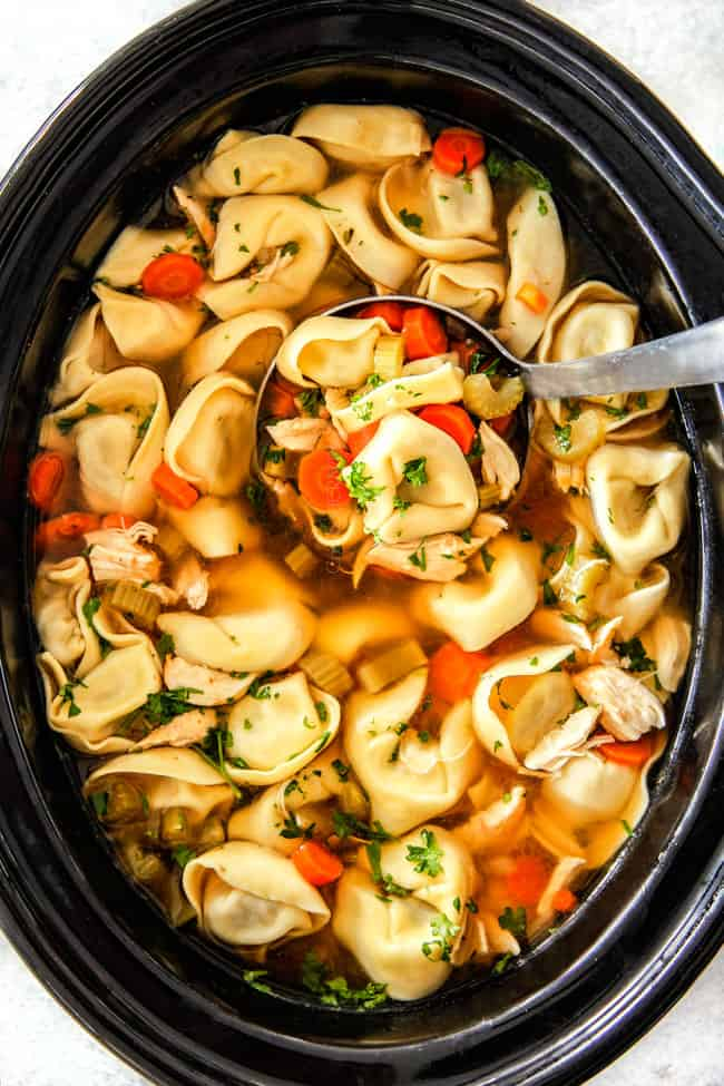 Chicken Tortellini Soup with cheese tortellini, carrots, celery, onions, garlic and spices in crockpot with soup ladle