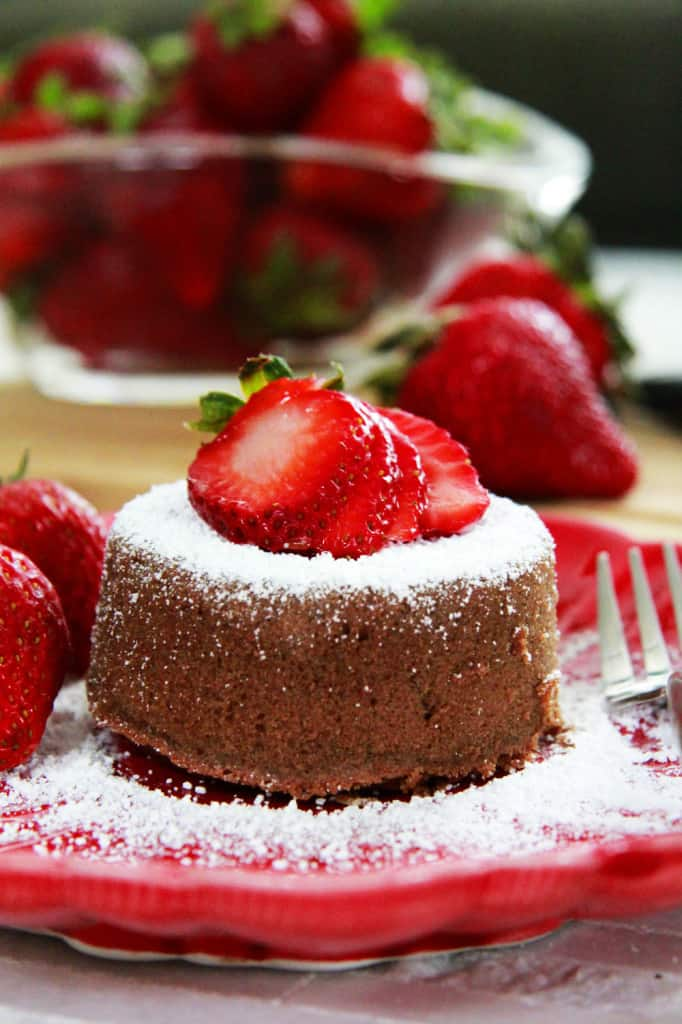 molten lava cake on a red plate topped with strawberries