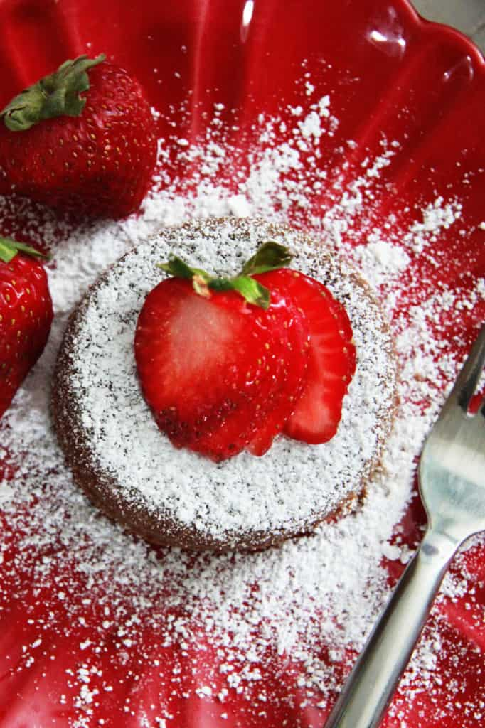 top view of molten lava cake with powdered sugar on a red plate