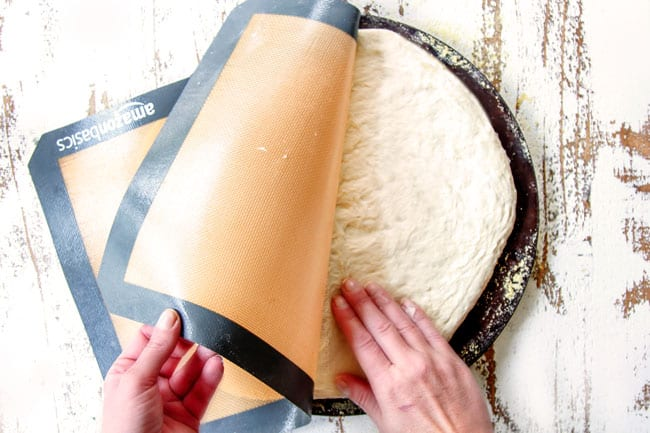 Showing how to make Homemade Pizza Dough by rolling dough onto a pizza stone