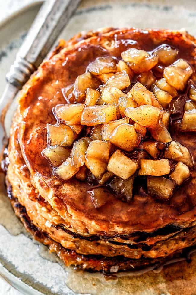 up close view of chunky cinnamon apple syrup on top of a stack of sweet potato pancakes