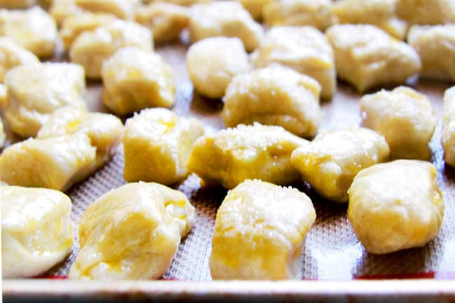 showing how to make Pretzel Bites by brushing them with butter and sprinkling with salt before baking