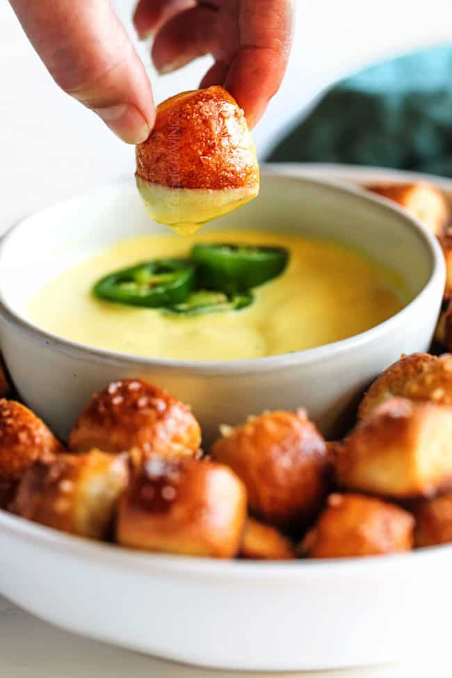 a hand holding onto a pretzel bite covered in cheese sauce