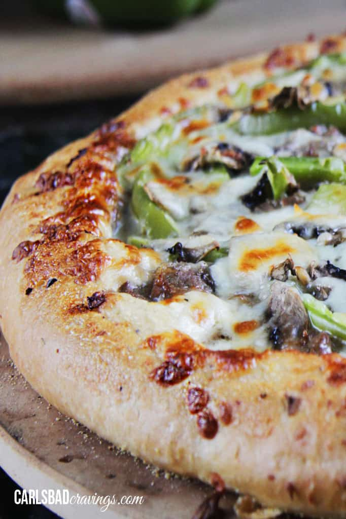 Alfredo Philly Cheesesteak Pizza on a round wooden platter.
