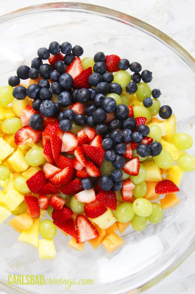 showing how to make fruit salad with yogurt by adding pineapple, grapes, blueberries, strawberries to a bowl