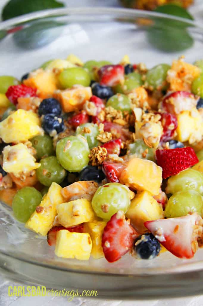 showing how to make fruit salad with yogurt by adding granola