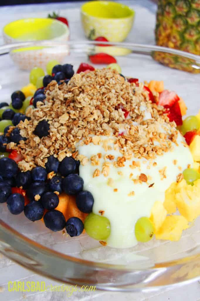 showing how to make fruit salad with yogurt by tossing fruit with yogurt