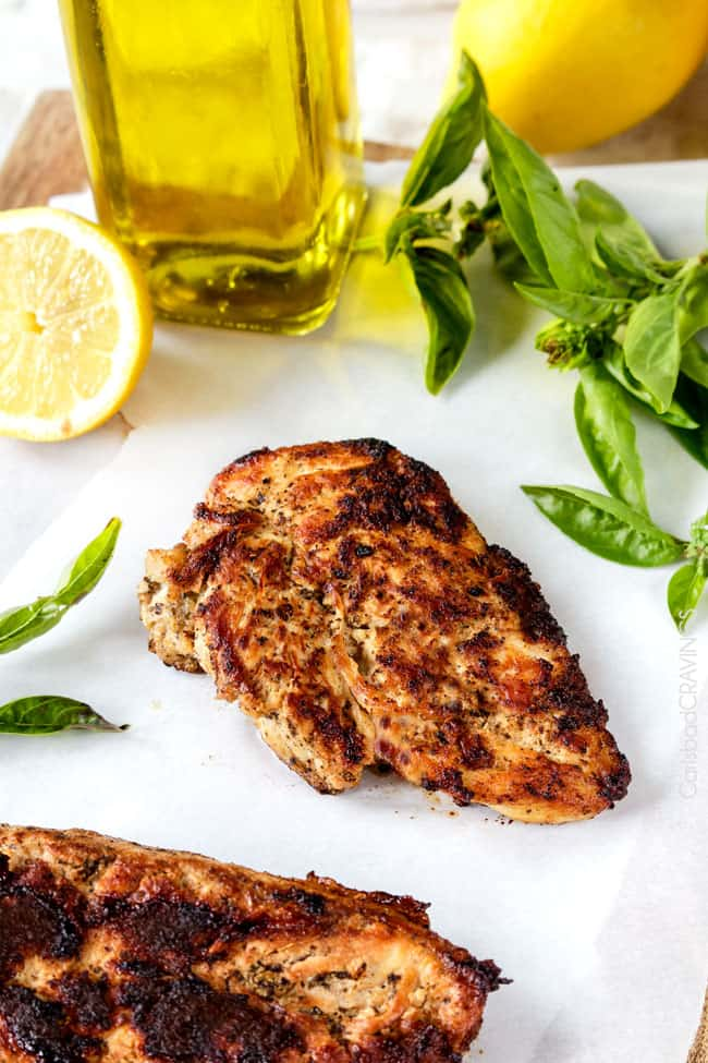 lemon herb chicken on a cutting board that has been marinated and cooked