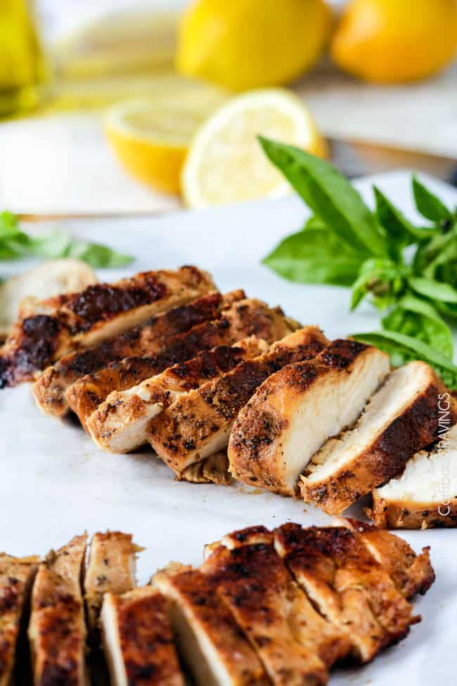 marinated lemon herb chicken thighs slice on a cutting board