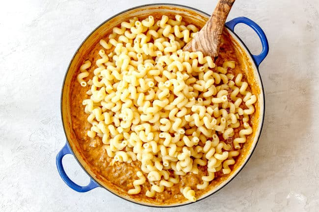 showing how to make buffalo mac and cheese by stirring in pasta