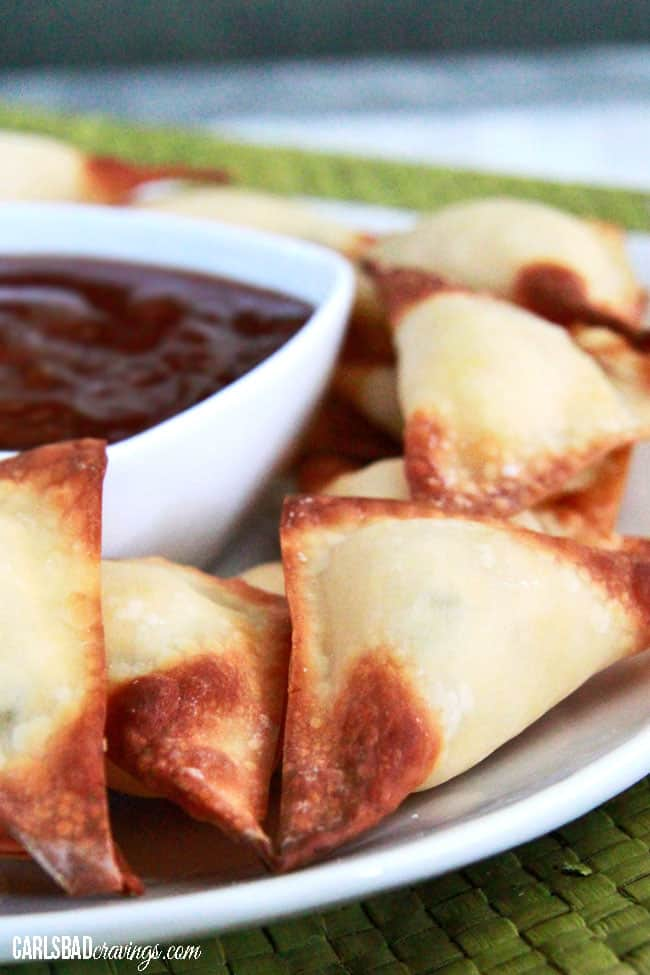 up close of easy cream cheese wontons on a white plate with sweet and sour dip