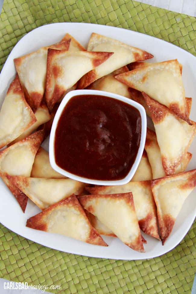 top view of garlic cream cheese wontons on a plate with sweet and sour sauce