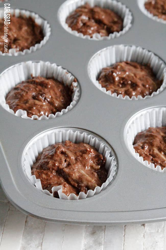 showing how to make chocolate zucchini muffins by adding batter to muffin tins