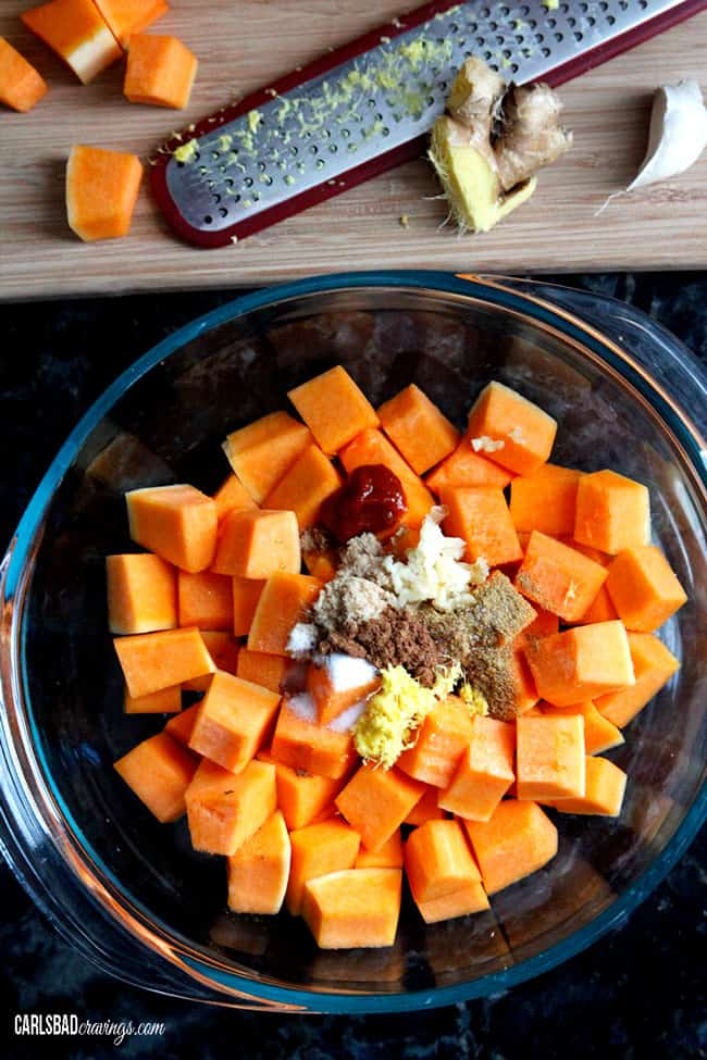 showing how to roast butternut squash by adding squash and seasonings to a glass bowl