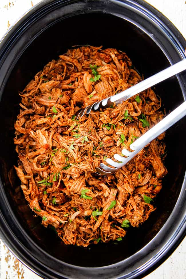 top shot of slow cooker cafe rio sweet pulled pork in crock pot with silver tongs