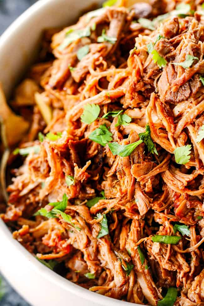 up close of chipotle sweet pulled pork in a white bowl with cilantro