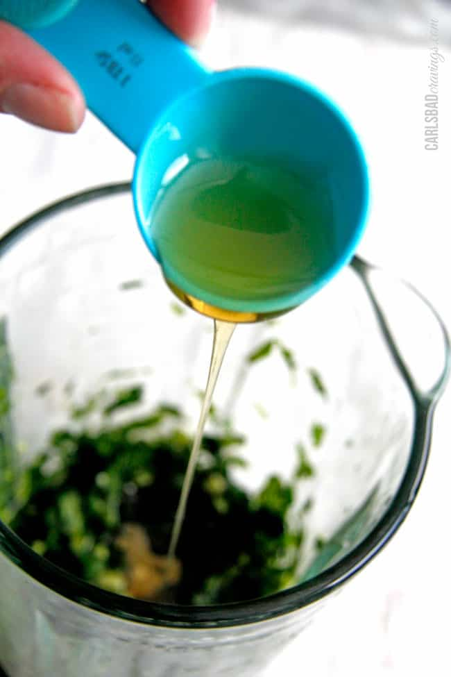 showing how to make chimichurri by adding oil to food processor