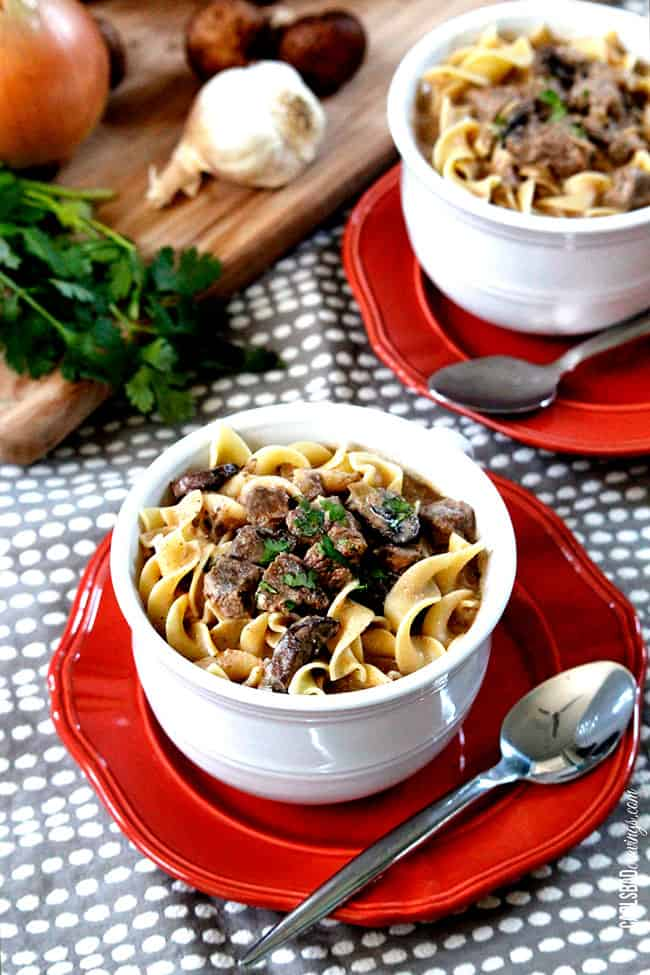 Beef Stroganoff Soup in a white with steak and parsley on top of egg noodles.