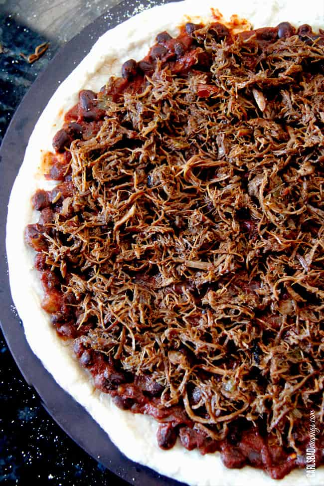 showing how to make pulled pork pizza by adding pulled pork to dough