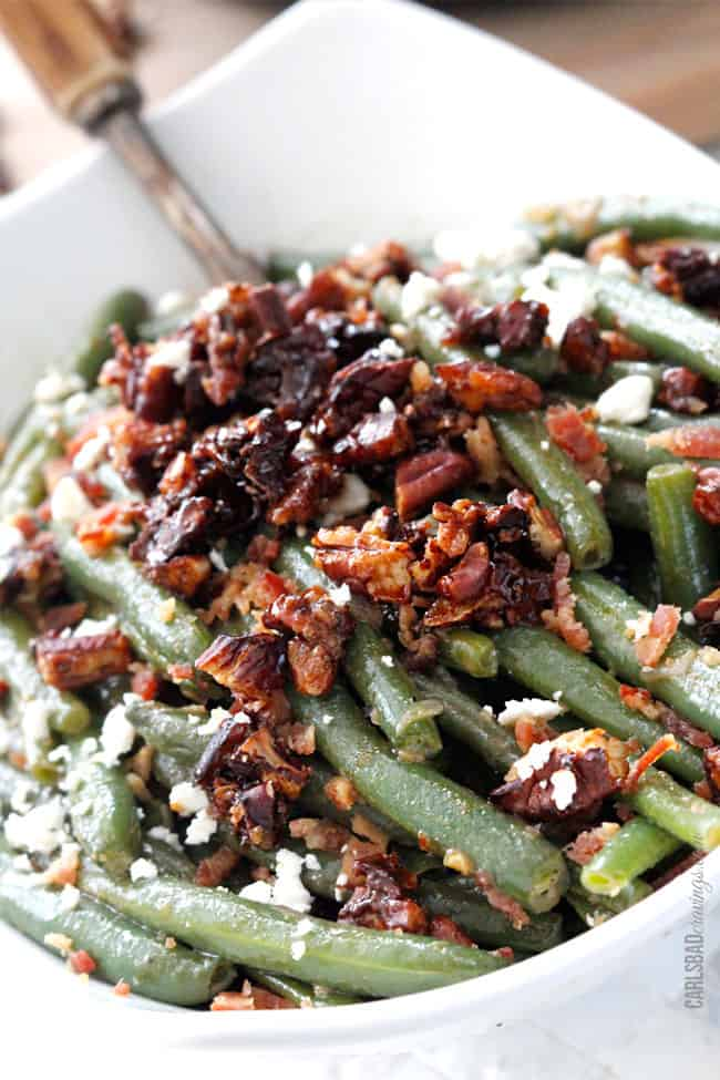 fresh green beans with bacon, pecans and feta in a white serving dish
