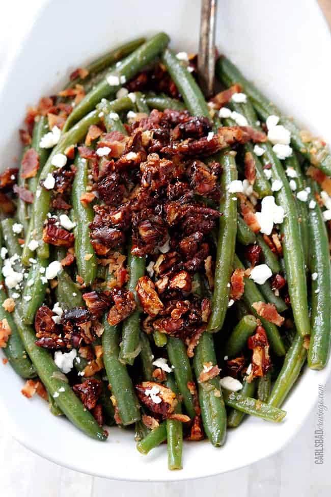 up close of fresh green beans with bacon in a white casserole dish