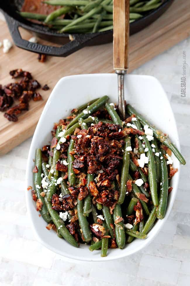 front view of green beans recipe with bacon and pecans with a wood serving spoon