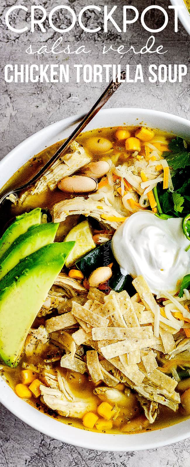 top up close of crockpot chicken torilla soup garnished with sour cream, avocados, cilantro and tortilla strips