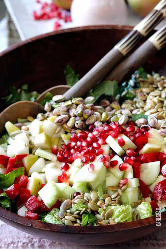 a winter salad with pears, apples, pomegranate arils, and more in a wood bowl
