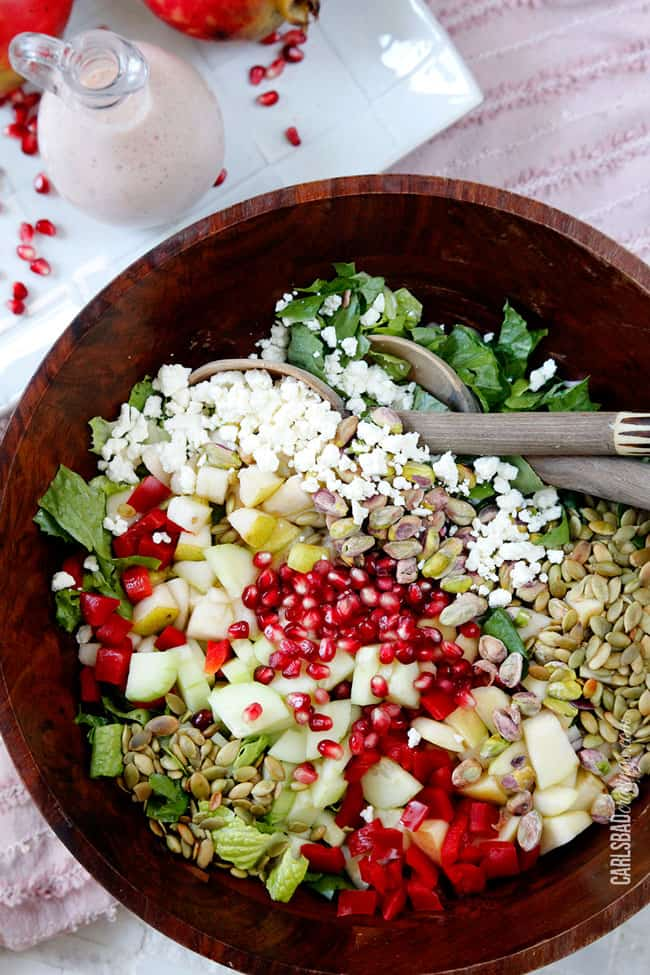 overhead view of a pear salad in a wood mixing bowl with salad spoons