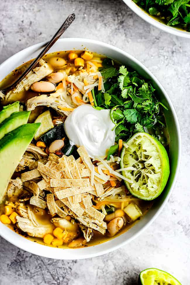 a bowl of easy crockpot chicken tortilla soup garnished with sour cream, avocados, cilantro and tortilla strips