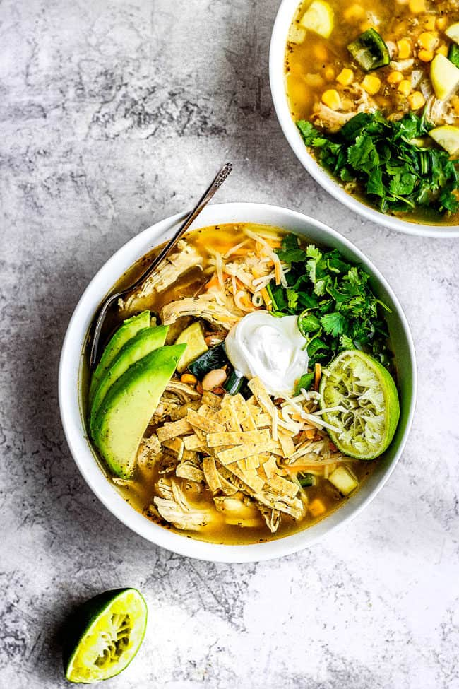 a bowl of healthy slow cooker chicken tortilla soup with homemade tortilla strips