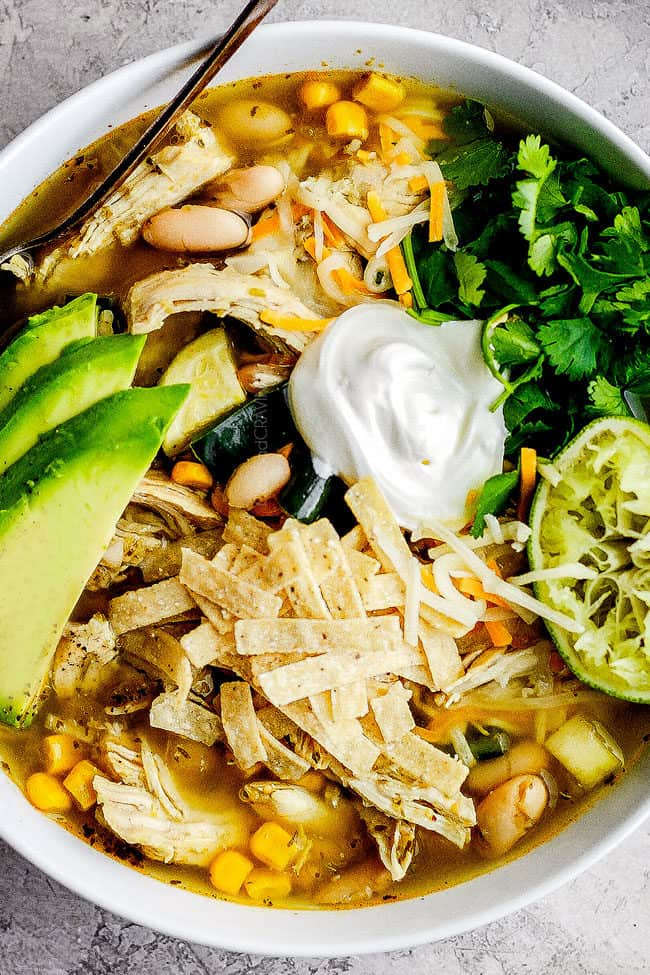 a bowl of slow cooker chicken tortilla soup garnished with sour cream, avocados, cilantro and tortilla strips