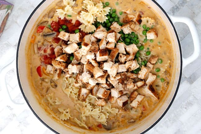 Showing how to make Cajun Chicken Pasta Soup in a white pot adding chicken and pasta to the sauce.