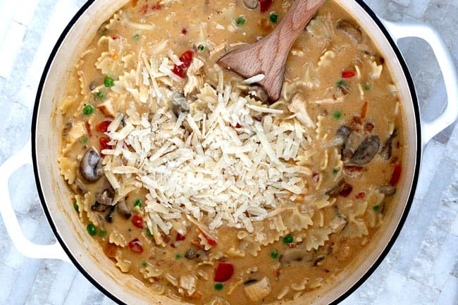 Showing how to make Cajun Chicken Pasta Soup in a white pot adding cheese.