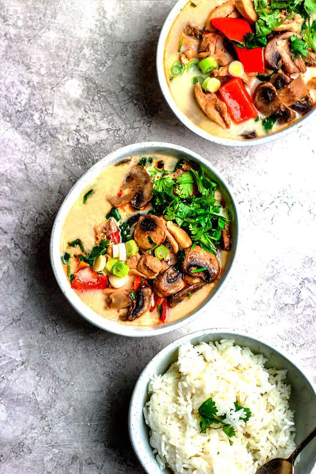 Top view of a bowl of gluten free Tom Kha Gai with a bowl of rice and cilantro garnishes