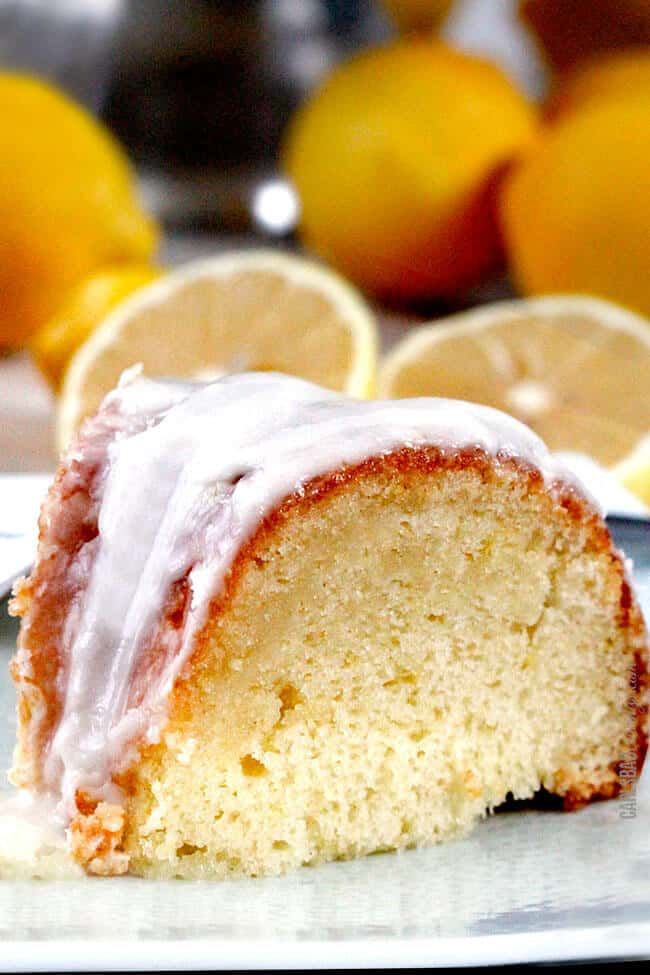 Slice of Lemon Poke Cake on a white serving plate with lemons in the background.