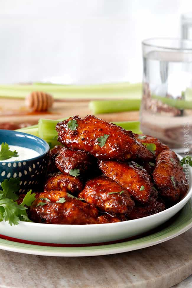 side shot of Honey Buffalo Hot Wings on a plate with celery and blue cheese dipping sauce.