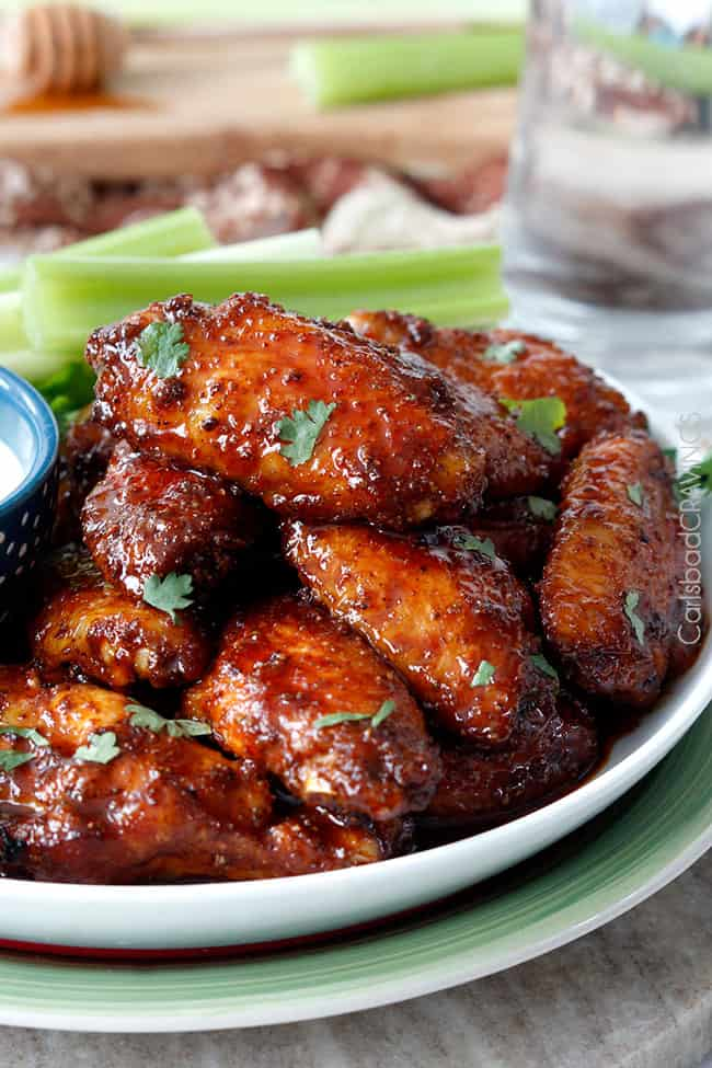 Honey Buffalo Hot Wings on a plate with celery dipping sauce, garnished with parsley.