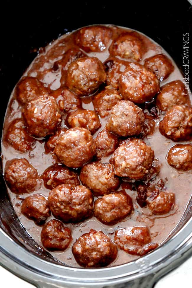showing how to make crockpot cranberry meatballs by simmering meatballs in sauce in the slow cooker