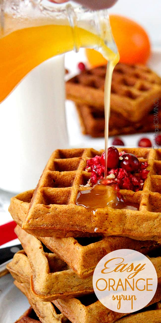 Orange Syrup being poured over top waffles with cranberries on top.