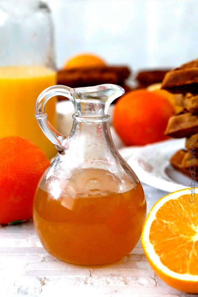 Orange Syrup in a clear jar nest to oranges and pancakes.