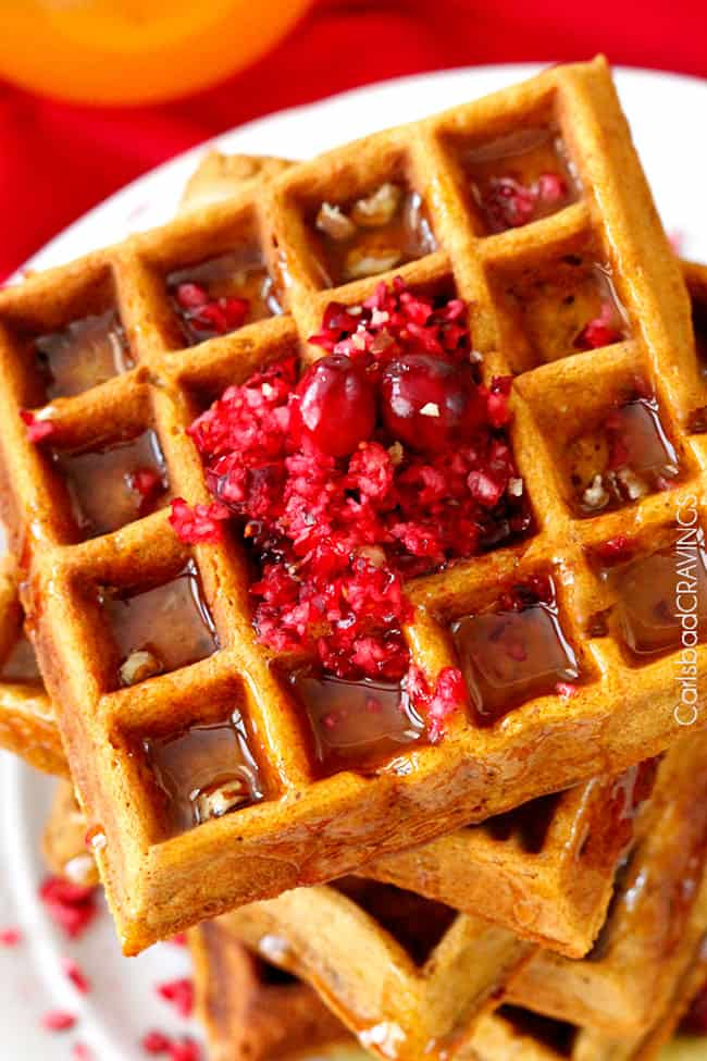 Close up of the Orange Syrup poured over a stack of waffles with cranberry garnish.